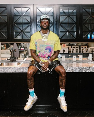 2 Chainz Wearing A Balmain Yellow Tee With Amiri Black Leather Shorts And Louis Vuitton Sneakers