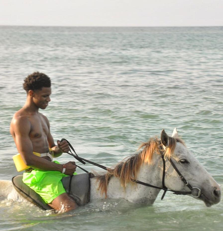 A Boogie In Jamaca Riding A Horse In Teh Ocean Wearing Versace Swim Shorts