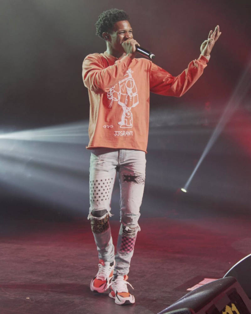 A Boogie Performing At Coachella Wearing A Jjgrant Orange Robot Shirt With Amiri Patch Jeans And White And Orange Puma Sneakers