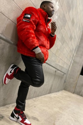Blac Youngsta Wearing A Red Supreme X The North Face Fur Puffer With Black Leather Pants And Jordan 1 Sneakers
