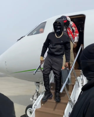 Bobby Shmurda Wearing A Prada Black Hoodie And Sneakers With A Louis Vuitton Briefcase