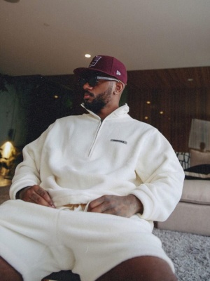 Bryson Tiller Wearing A Fear Of God Essentials Fleece Sweatshirt And Shorts With A New Era Burgundy Hat