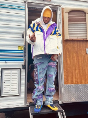Chris Brown Wearing A Yellow Bape Beanie White Nike Lakers Jacket And Mismatching Nike Sneakers