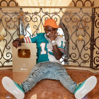Dababy Showing Off His Youtube Gold Award In A Split Dan Marino Jersey Amiri Jeans And Teal Nike Sneakers
