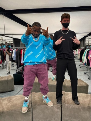 Dababy Wearing A Balenciaga Swater With Burgundy Cago Pants And Jordan X Union Taupe Haze Sneakers