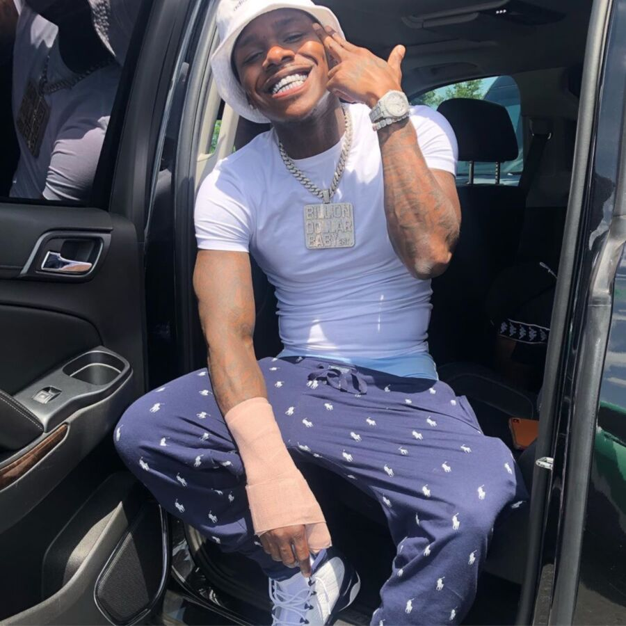 Dababy Wearing A White Adidas Bucket Hat Navy Polo Pants And White And Black Jordans