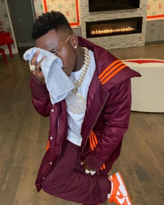 Dababy Wearing An Adidas X Ivy Park Puffer And Pants With Orange And White Nikes And Gucci Glasses