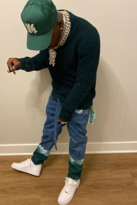 Dababy Wearing An Amiri Green Logo Trucker Hat With A Green And Black Striped Sweater And Off White Blaeched Cuff Jeans