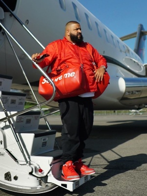 Dj Khaled Wearing A Lv X Supreme Duffle Bag With Nike Joggers And Red Jordan 3s