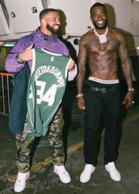 Drake In A Puprpel Jacket White Nike And Camo Pants With Gucci Mane In A Green Basketball Jersey