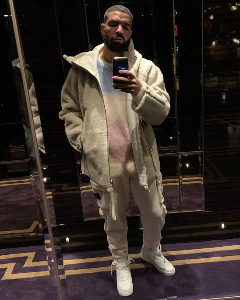 Drake Wearing A White Sherpa Jacket With Isabel Marant Sweater And Stone Island Pants