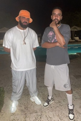 Drake Wearing An Stone Island Orange Bucket Hat And White Tee With Silver Pants And Grey Red Nike Sneakers