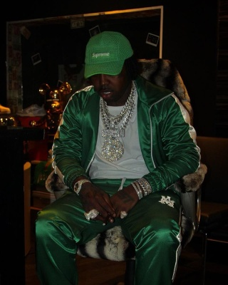 Est Gee Wearing A Supreme Green Crocheted Hat With An Amiri Track Jacket And Track Pants