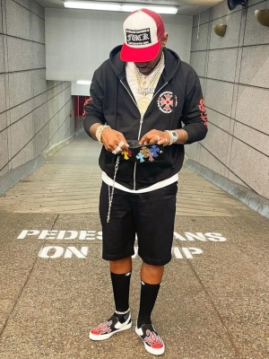 Fabolous Wearing A Red Chrome Hearts Trucker Hat With A Black Zip Hoodie And Socks And Amiri Slip On Sneakers