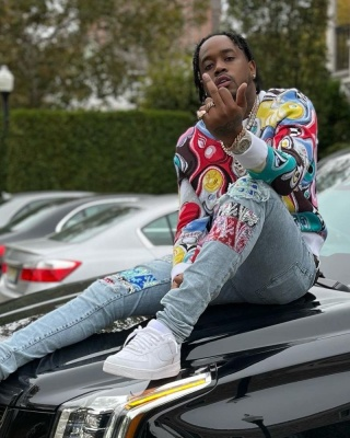 Fivio Foreign Wearing A Dior X Kenny Scharf Multicolor Sweater With Amiri Paisley Patch Jeans And Nike Air Force 1s