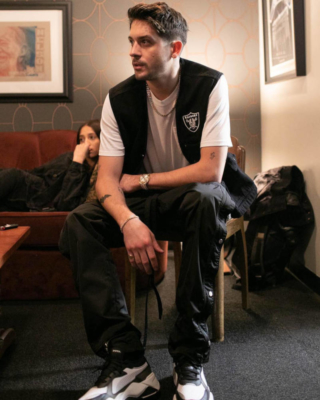 G Eazy Wearing A Black Denim Supreme Oakland Raiders Vest And Puma Rs X Tech Sneakers