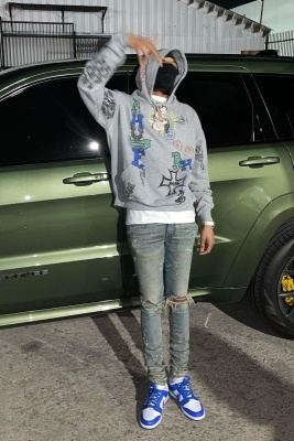 G Herbo Wearing A Rhude Marker Print Hoodie With Amiri Jeans And White And Blue Jordan Low Top Sneakers