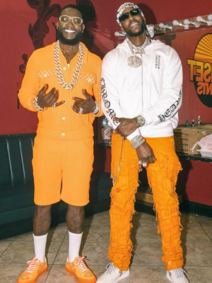 Gucci Mane Wearing An Orange Louis Vuitton Jacket Shorts And Sneakers At Superbowl 55