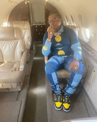 Gunna Flies Private In A Kapital Denim Shirt And Blue Tee With Patchwork Jeans And Jordan 1 Mid Navy Yellow Sneakers