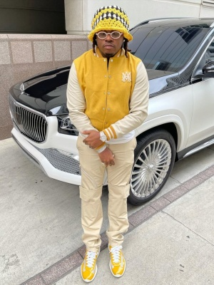 Gunna Wearing A Yellow And White Amiri Varsity Jacket And Crochet Hat With Prada Sneakes