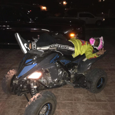 Incorporated Style Cover Iage For Juice Wrld Sitting On Top Of His Atv Wearing Supreme X Comme Des Garcons Sneakers And Black Dolce And Gabbana Pants And A Yellow Suzuki Racing Shirt