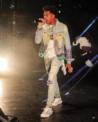 Incorporated Style Instagram Post Of Lil Baby Wearing Amiri Hollywood Jacket Amiri Hollywood Keychain Amiri Lightwash Ripped Skinny Jeans With Multicolored Underpatches And Dior Floral Sneakers