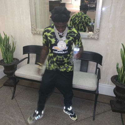 Instagram Post Of Kodak Black Wearing A Black And Green Animal Print Adidas Top With A Printed Chevrolet Logo And Black And Green Adidas Tresc Sneakers