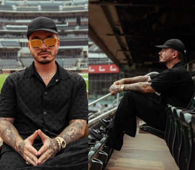 J Balvin Wearing A Black Prada Hat With A Louis Vuitton Black Monogram Shirt And Pants And Ollie Sneakers
