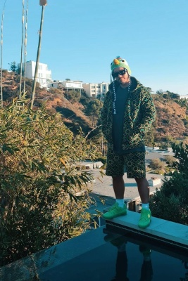 J Balvin Wearing A Louis Vuitton Jamacian Hoodie And Shorts With Black Classic Sunglasses And Neon Green Sneakers