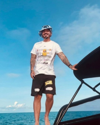 J Balvin Wearing An Advisory Board Crystals Merch Tee And Off White Spray Paint Shorts