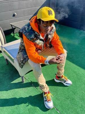 Jackboy Wearing An Amiri Yellow Trucker Hat With A Celine Camo Puffer Orange Hoodie And Dior Sneakers