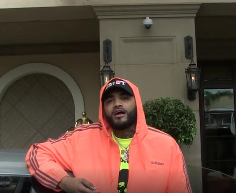 Joyner Lucas Talking To Tmz In An Orange Adidas Windbreaker And Yellow The Hundreds Printed Shirt