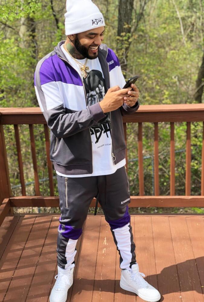 Joyner Lucas Wearing A Grey And Purple Track Jacket And Track Pants With White Adhd Beanie And T Shirt
