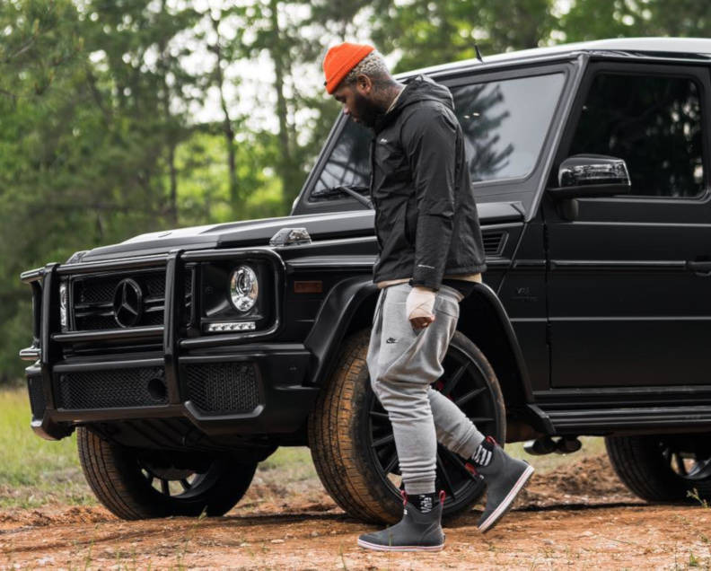 Kevin Gates Doing Some Farming Wearing A Black Columbia Windbreaker With Grey Nike Joggers An Orange Knit Beanite And Navy Xtratuf Ankle Boots