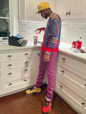 Key Glock Wearing A Louis Vuitton Sweater And Purple Jeans With An Audemars Piguet Camo Watch And Jordan Mismatching Sneakers