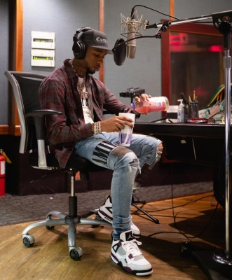 Key Glock Wearing An Amiri Flannel Shirt With A White T Shirt And Jeans And Jordans