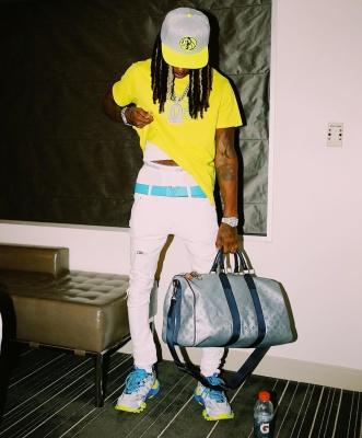 King Von Wearing A Yellow Givenchy Tee White Amiri Jeans Blue Lv Belt White Amiri Jeans Balenciaga Track Sneakers And A Louis Vuitton Duffle Bag