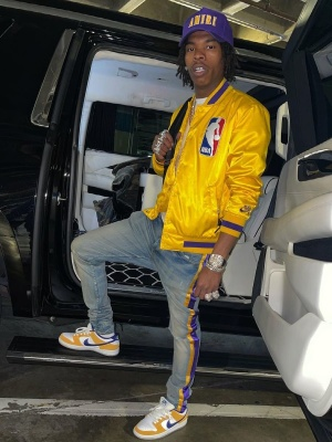Lil Baby Wearing An Amiri X Lakers Hat And Jeans With A Nike Sb Lakers Bomber And Nike Dunk Yellow And Puprle Sneakers
