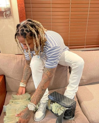 Lil Durk Wearing A Dior Striped T Shirt With A Dior X Jordan Sneakers And A Louis Vuitton Bag