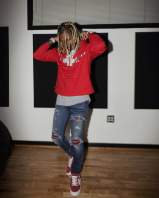 Lil Durk Wearing A Red Hoodie With Matching Amiri Jeans And Suede Sneakers