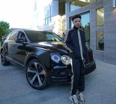 Lil Mosey Wearing A Gucci Tracksuit And Sneakers In Front Of His Bentley