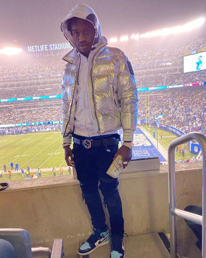 Lil Tjay Attends The Ny Giants Game In A Moose Knuckles Metallic Puffer Gucci Belt And Patent Jordans