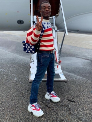 Lil Uzi Vert Wearing A Saint Laurent American Flag Sweater And Backpack With A Chanel Belt And White Prada Sneakers
