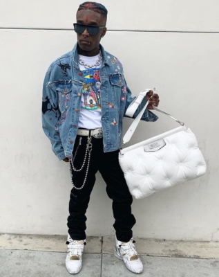 Lil Uzi Vert Wearing A Vetements Denim Jacket Maison Margiela Bag And Sneakers With Dior Pants And Lsd Print Shirt And Vivienne Weatwood Belt