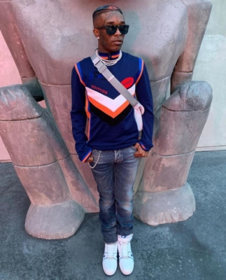 Lil Uzi Vert Wearing Louis Vuitoon Sunglasses Shirt And Sneakers With Dior Jeans And An Lv Bag