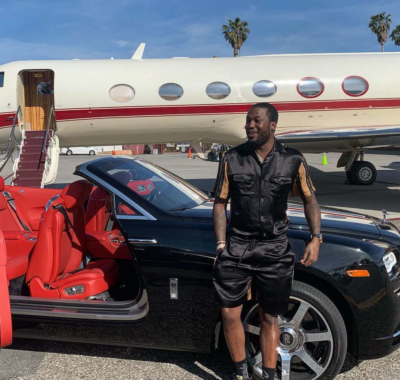 Meek Mill Standing Infront Of A Jet And Next To A Rolls Royce Drop Top Wearing A Black Gucci Shirt And Black Gucci Shorts