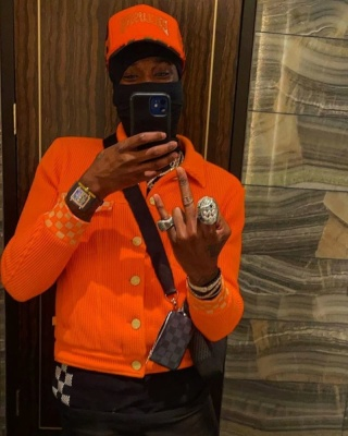 Meek Mill Wearing A Louis Vuitton Orange Jacket And Black Tee With A Richard Mille Watch