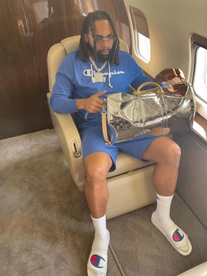 Money Man Wearing A Champion Hoodie Shorts And Slides With A Louis Vuitton Mirror Bag