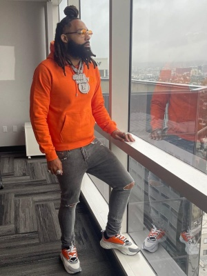 Money Man Wearing A Dior Orange Cd Icon Hoodie With Grey Jeans And Dior Orange White Black B22 Sneakers