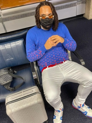 Money Man Wearing A Louis Vuitton Sweater With A Red Belt White Jeans Matching Sneakers And Louis Vuitton Bags